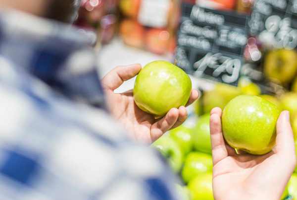 Comparing two apples in a grocery store