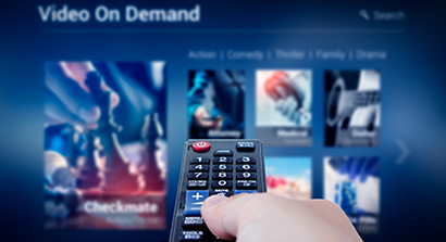 VOD service screen with remote control in hand and video on